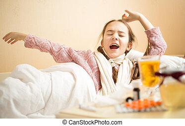 little girl with flu yawning in bed at morning - Portrait of...