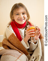 smiling girl in scarf covered in plaid holding cup of hot...