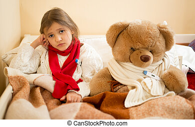 sad girl measuring temperature with teddy bear in bed -...