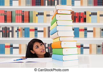 Woman Looking At Stack Of Books