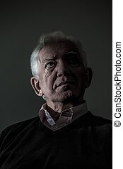 Thoughtful sad elder man on dark background