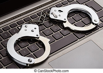 Internet Crime - Photo Of Handcuffs Lying On Laptop Keypad