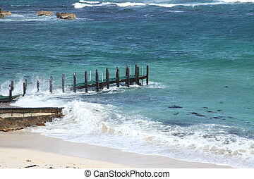 Pier choppy seas - Wooden pier on beach with choppy blue...