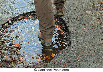Close-up of a large pothole - Close-up of a man walking...