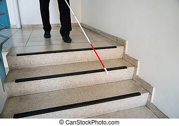 Blind Man Moving Down On Stairway Holding Stick