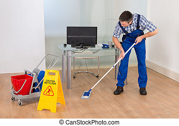 Man Mopping Office With Wet Floor Sign - Portrait Of A Male...
