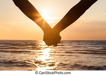 Couple Holding Hands At Beach - Cropped image of couple...