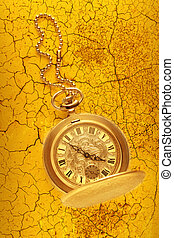 Golden pocket watch with chain on cracked background