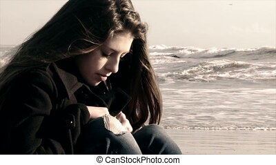 thoughtful female teenager sitting on the beach in cold...