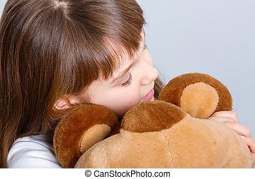 girl hugging bear - A portrait of a young pretty girl...