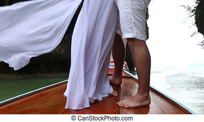groom and bride stand on longtail boat in sea near cliff -...