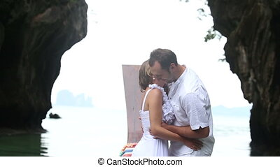 bride and groom stand and kiss in wooden boat