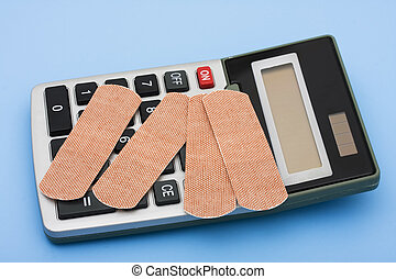 Calculating Healthcare Costs - A calculator and bandages on...