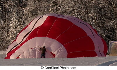 Workers straighten fabric of hot air balloon