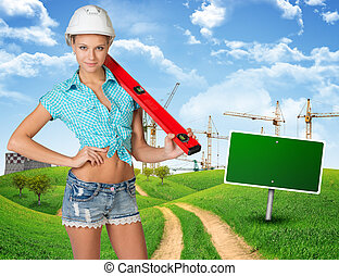 Woman in hard hat, holding large spirit level on her...