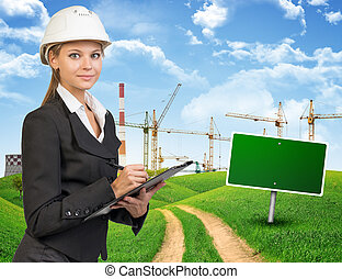 Businesswoman in hard hat, writing on clipboard -...