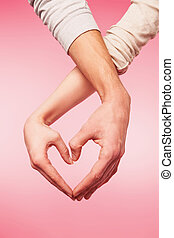 Closeup of woman and man hands showing heart shape - love...