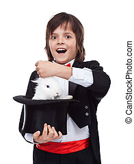 Young magician boy taking a rabbit out of his hat