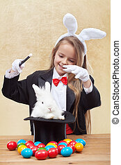 Happy magician girl conjuring up the easter bunny and eggs -...