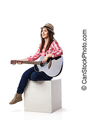 Woman is sitting and playing her guitar - Beautiful brunette...