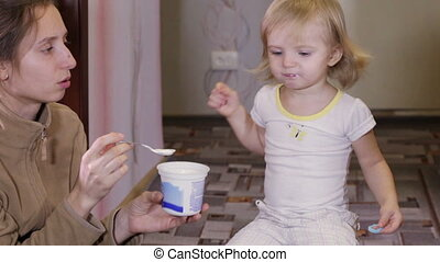 Feeding baby - Young mother feeds her baby with yogurt