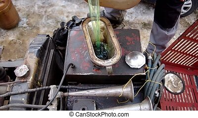Pouring the diesel into the tractor from canisters through...