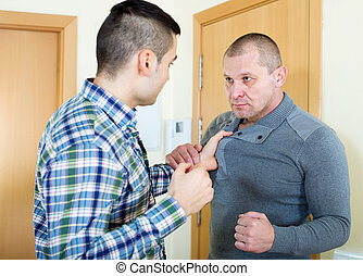 Two angry men looking at each other with clenching fists