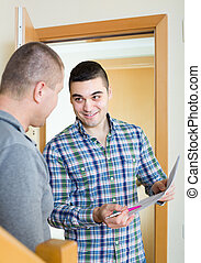 Service employee with tenant at doorway - Smiling service...