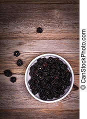 Blackberries - A white bowl filled with blackberries on an...