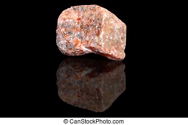Orange calcite raw mineral stones with reflection on black...