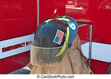 firefighter helmet on coat - Firemans helmet on coat by red...