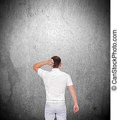 businessman thinking and looking on gray concrete wall