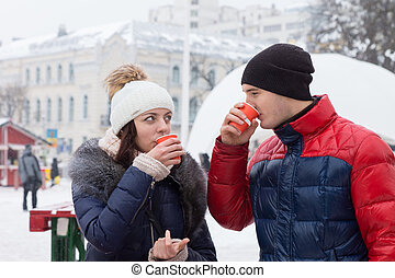 Couple sipping hot drinks in a wintry town square - Young...