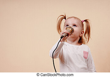 Girl Singing - Little girl holding microphone and singing,...