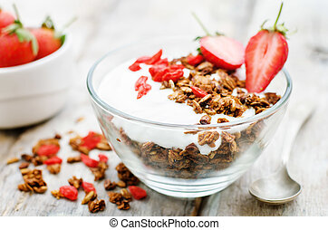 fresh breakfast of granola, yogurt, nuts, goji berries and...
