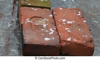 Snowing flakes over laying bricks outdoors