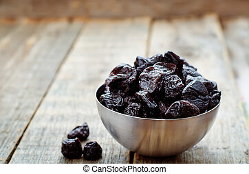 prunes in a bowl on a dark wood background. tinting....