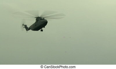 Close-up of military helicopter flying in cloudy sky