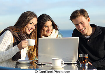 Group of friends watching a laptop in a restaurant terrace...