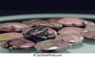 Rhodonite carved stone hearts are rotating on a glass plate...