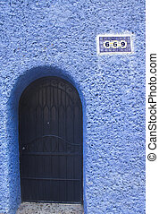 black door in blue wall