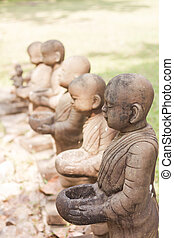 Little monk clay doll decorated in garden, stock photo