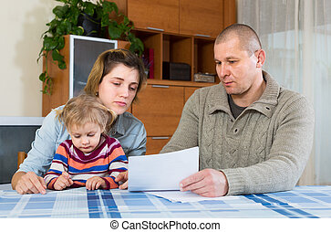 Worried family with financial documents - Worried couple...