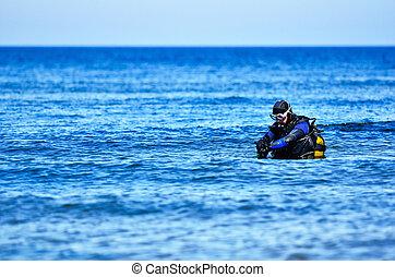 Scuba diving - Scuba diver preparing to dive into sea