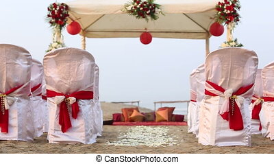 wedding decorated tent spectators seats rose petals on ocean...