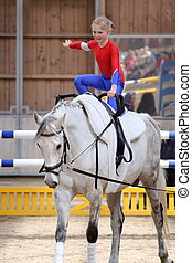 young girl is vaulting on a big white horse