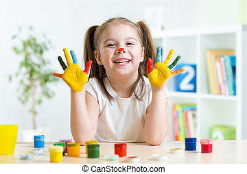 Girl having fun, her palms covered with paint - Kid girl...