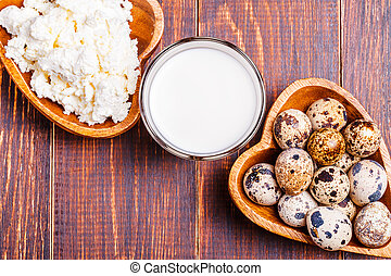 Quail eggs, cottage cheese, milk on a wooden brown...