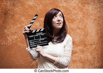 Young woman 70s hippie style closeup with clapperboard -...