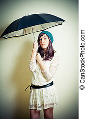 Young woman in 70s hippie style posing with umbrella vintage...